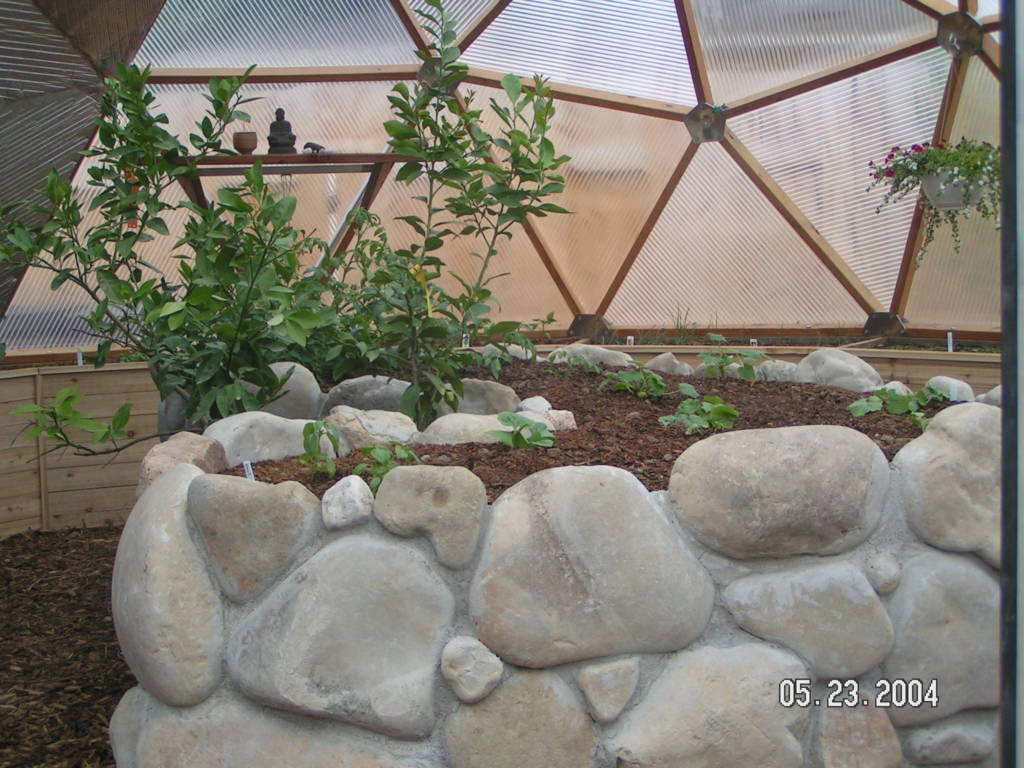 rock and concrete center raised bed in Growing Dome greenhouse