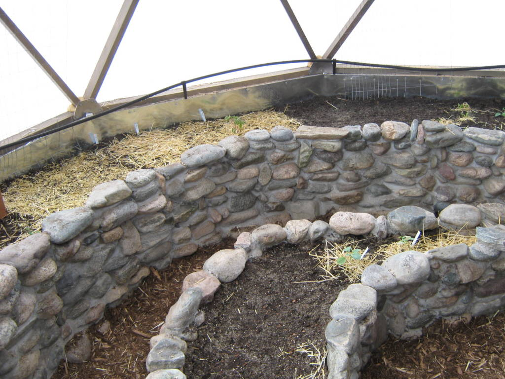stone planting bed in geodesic dome greenhouse