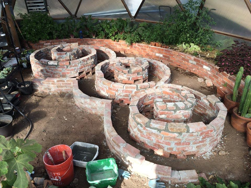 spiral brick planting beds in geodesic dome greenhouse