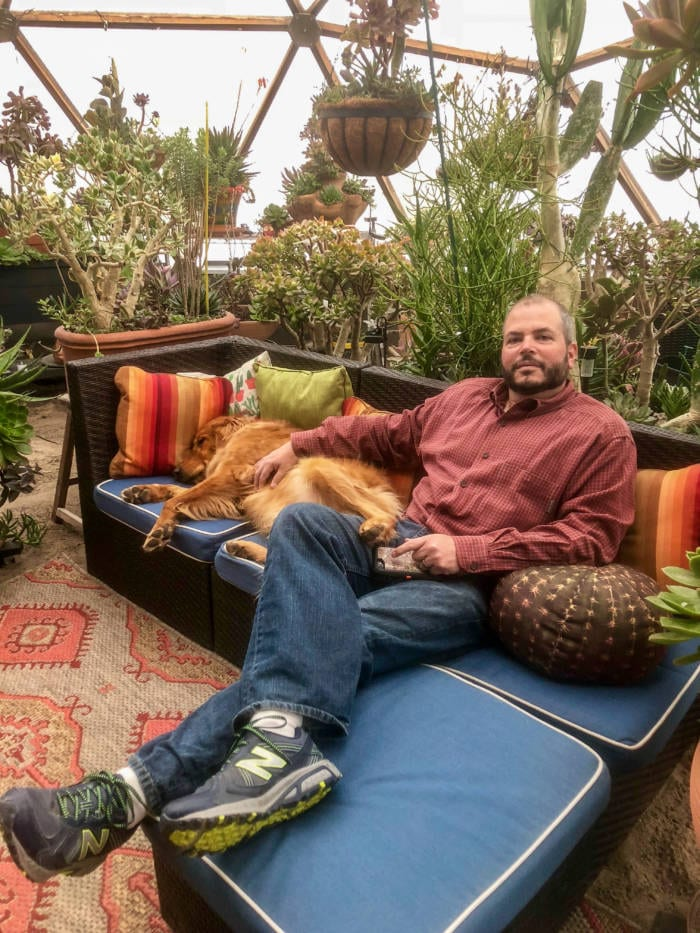 Daniel relaxing in Growing Dome Greenhouse with dog and a variety of succulents