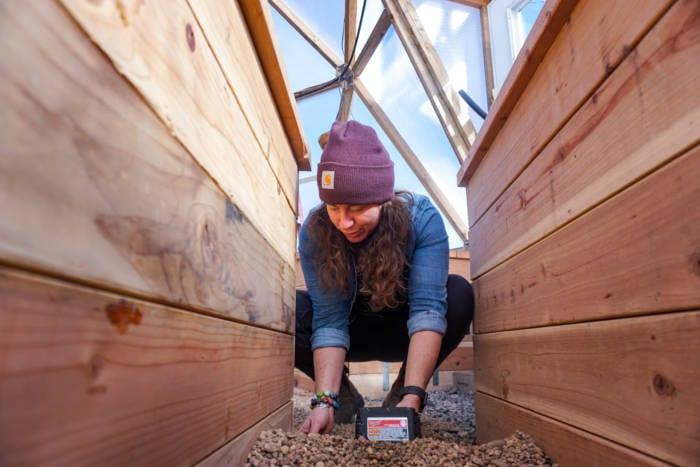 GoFarm Farmer Apprentice Shannon Harker installing a drip irrigation system in a Growing Dome